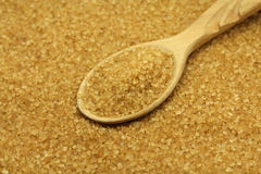 Crumbly sugar in a wooden spoon  background Royalty Free Stock Photography