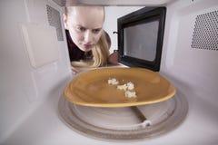 Crumbs ψωμιού στο πιάτο στο μικρόκυμα Το κορίτσι εξετάζει το φούρνο Στοκ φωτογραφίες με δικαίωμα ελεύθερης χρήσης