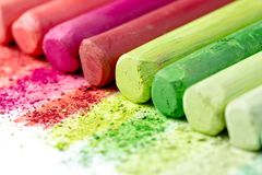 Crumbs and chunks of multicolored chalk, pastels on white paper for watercolor. Yellow, pink, red, green, gray, light green crimso. N stock image