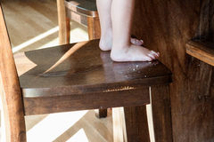 Crumbs next to child's feet on dining room chair Stock Image