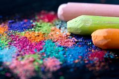 Crumbs van multi-colored krijt op een zwarte achtergrond Vreugde, Carnaval, Panorama Een spel voor kinderen Art royalty-vrije stock fotografie
