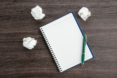 Crumple paper and pen with notebook on the desk Stock Image