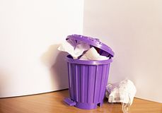 Trash can is full. Crumple paper in trash can.Trash can is purple colour. White backgrounds royalty free stock photo
