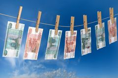 Crumpled banknote of roubles to dry on the rope clothes pins attached Stock Photos