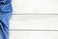 Crumpled blue checkered tablecloth or napkin on empty white wood Stock Image