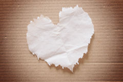 Crumpled brown  tissue paper (heart shape). On cardboard Stock Photo