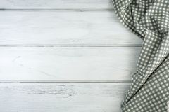 Crumpled checkered tablecloth or napkin on empty white wooden ta. The Crumpled checkered tablecloth or napkin on empty white wooden table with copy space for Royalty Free Stock Image