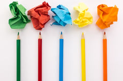 Crumpled colored paper on a white background with colour pencils Stock Images