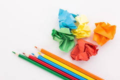Crumpled colored paper on a white background with colour pencils Royalty Free Stock Images