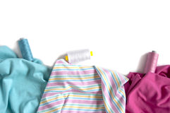 Crumpled colorful fabrics with colour-matched threads  for tailoring Stock Photo