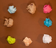 Crumpled colorful paper on brown background Stock Photos