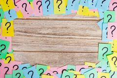 Crumpled colorful paper notes frame with question marks.  Royalty Free Stock Image