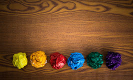 Crumpled colorful paper. On wooden background stock photos