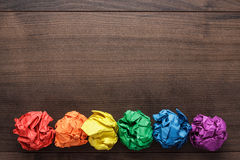 Crumpled colorful paper on wooden background stock photos