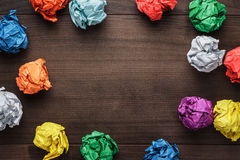 Crumpled colorful paper on wooden background royalty free stock photos