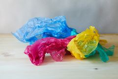Crumpled colorful plastic bags and wraps on wooden table. Used crumpled colorful plastic bags and wraps on wooden table stock photo