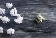 A crumpled dollar on a table next to white paper balls. The process of thinking and finding new business ideas. Profitable solutions. Attraction of investments Royalty Free Stock Photography