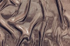 Crumpled fabric of glossy chocolate color Royalty Free Stock Photo