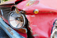 Crumpled fender and a broken headlight. On a red vintage car Royalty Free Stock Images