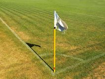 Crumpled flag in corner of footbal playground, lazy wind blowing, sharp shadow. On the dry grass Royalty Free Stock Photography