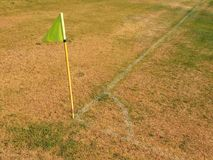 Crumpled flag in corner of footbal playground, lazy wind blowing, sharp shadow. On the dry grass Stock Photos