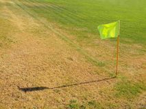 Crumpled flag in corner of footbal playground, lazy wind blowing, sharp shadow. On the dry grass Stock Photography