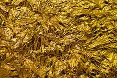 Crumpled golden foil. Metallic abstract background stock photo