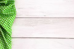 The Crumpled green checkered tablecloth or napkin on empty white. Crumpled green checkered tablecloth or napkin on empty white wooden table with copy space for Royalty Free Stock Images
