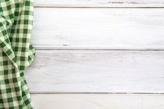 The Crumpled green checkered tablecloth or napkin on empty white. Crumpled green checkered tablecloth or napkin on empty white wooden table with copy space for Stock Images