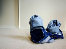 Crumpled Jeans on the Floor. A pair of jeans crumpled on the floor after a day of wear stock photo