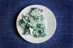 Crumpled money on a plate. Blue background royalty free stock photography