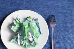 Crumpled money on a plate,. Blue background stock image