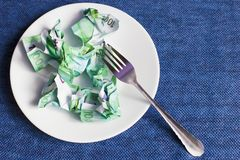 Crumpled money on a plate,. Blue background stock photography