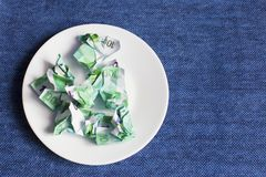 Crumpled money on a plate, Stock Image