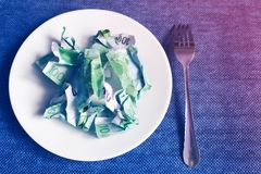 Crumpled money on a plate. Blue background stock photos