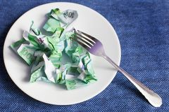 Crumpled money on a plate. Blue background royalty free stock photos