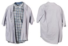 A crumpled old checkered and solid gray  man`s shirts  hangs on. A hanger. View from two sides. Isolated on white studio set Royalty Free Stock Photo