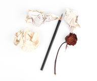 Crumpled old papers and pencil with wilting rose Stock Photography