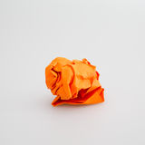 Crumpled orange paper ball. White background Royalty Free Stock Photography