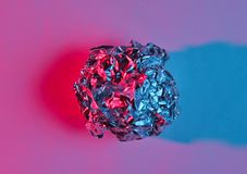 Crumpled paper ball enveloping neon blue pink light. Top view, surrealism royalty free stock photos