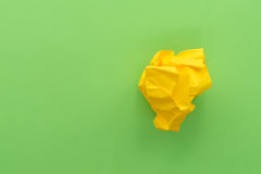Crumpled paper ball on green paper background Royalty Free Stock Image