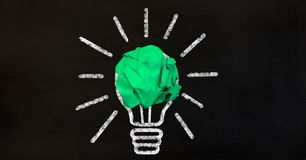 Crumpled paper ball with light bulb concept Royalty Free Stock Images
