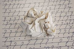 Crumpled paper ball and question marks on sheet of lined paper Royalty Free Stock Photos