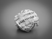 Crumpled paper ball with words Friendship on gray background Stock Images