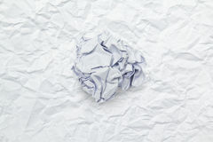 Crumpled paper ball on wrinkled paper Stock Image