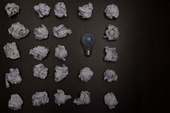 Crumpled paper balls and blank sheet of paper with pencil on black background. Paper wad. Creativity problems. Searching Royalty Free Stock Photo