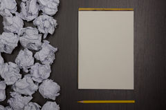 Crumpled paper balls and blank sheet of paper with pencil on black background. Paper wad. Creativity problems. Searching Royalty Free Stock Photos