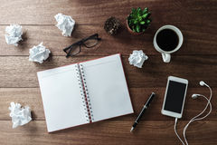 Crumpled paper balls with cup of coffee and notebook on wooden d royalty free stock photos