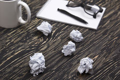 Crumpled paper balls with eye glasses mug, pen and notebook Stock Photos