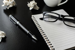 Crumpled paper balls with eye glasses and notebook Royalty Free Stock Photo